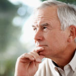 Contemplative senior man with hearing loss looking away