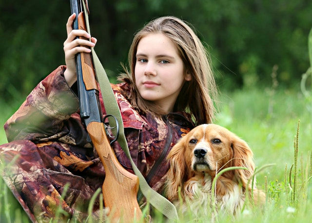 woman with a hunting rifle and her dog