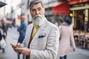 Older bearded male looking off into the distance with a cellphone in his hand