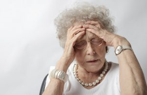 Older woman with her hands on her forehead in a stressed out manner