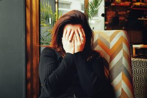 Woman holding her hands to her face.