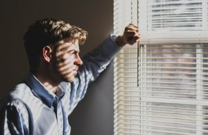 Depressed man looking outside of a window.