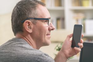Man with hearing aids uses a smartphone.